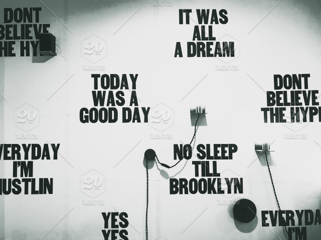 "A modern office wall, covered with slogans which read ""today"
