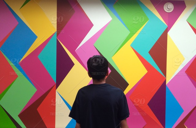 Boy Standing In Front Of A Colorful Wall Mural Colorful
