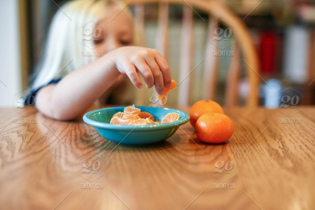 Little Girl At The Kitchen Table Eating Clementines For A