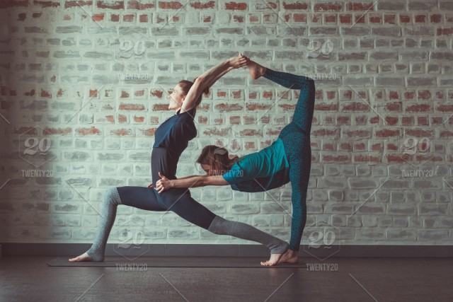 Two Young Beautiful Women Practising Yoga Poses In Yoga Class Against Brick Wall Stock Photo 299a2ae9 F9b1 4861 97e7 8c7e7fb15c1f
