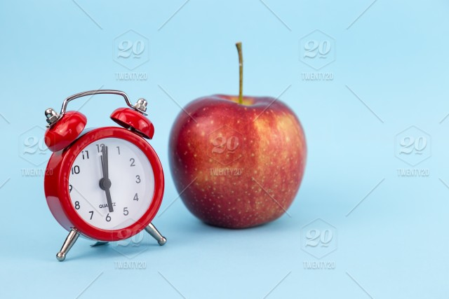 Red apple and retro alarm clock on blue color background