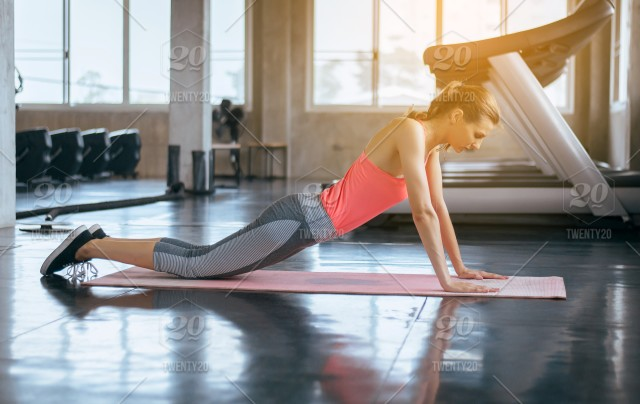 Strong and slim woman doing push up exercises on yoga mat
