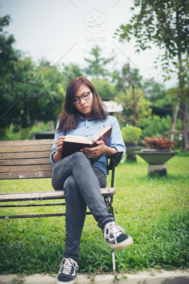 Hipster Charming Girl Relaxing In The Park While Read Book