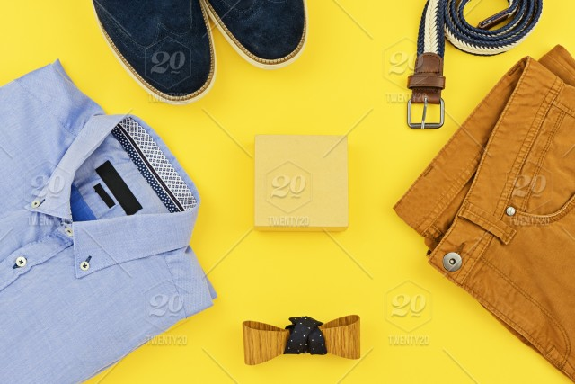 a67175100f007 Casual outfits for man clothing with blue shirt, mustard jeans, belt,  watch, blue shoes and accessories isolated on yellow background, top view.