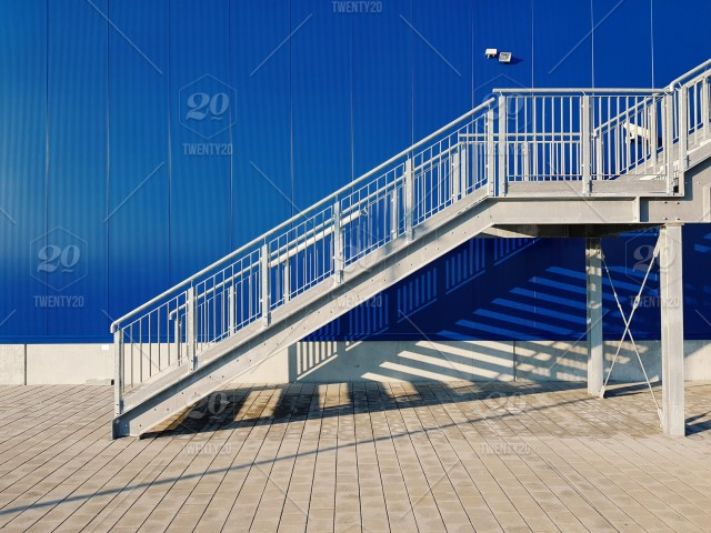 Metal staircase construction with a blue building in the back