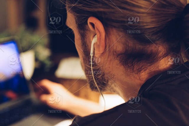 e6de0962edc Man working by the computer with earplugs in his ears stock photo ...