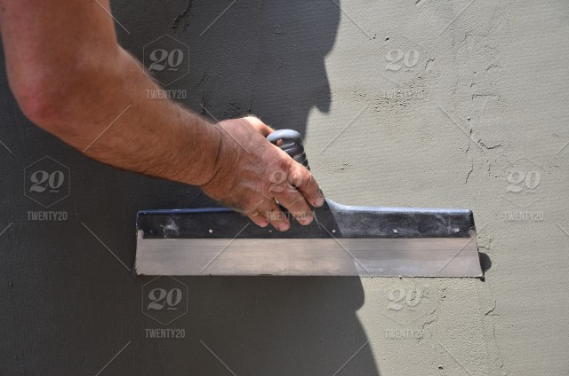 Hands of an old manual worker with wall plastering tools renovating