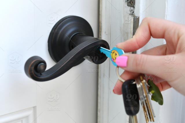 Using a key to unlock the door  Copy space, real people