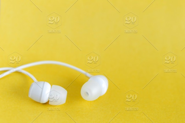 White earbuds on yellow colorful monochrome background with copy