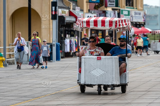 A Pedicab Pushes His Customers Past The Boardwalk Lined With