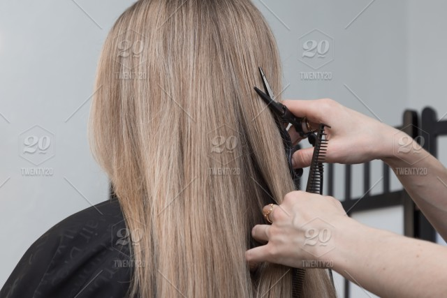 The Hairdresser Does A Haircut With Hot Scissors For A Girl With