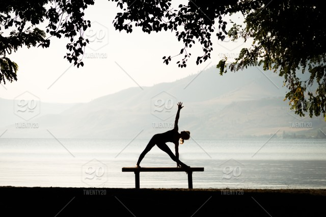 A Woman In Silhouette Doing A Yoga Pose On A Bench Stock Photo 76ce602a 8eda 4b64 895a 3ec01c275cd1