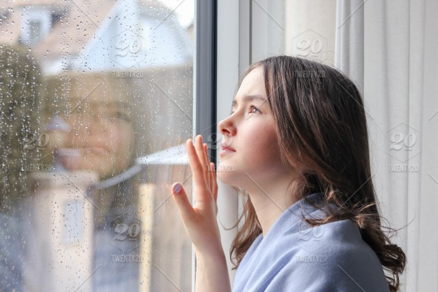 Beautiful Tween Girl In Light Blue Scarf Looking Outside Through Raindrops On Wet Window At Sky Spring Rainy Day Waiting For Sun Seasonal Weather Concept Stock Photo 1d9f5ca0 6e11 4720 B381 0fcd20b779a6