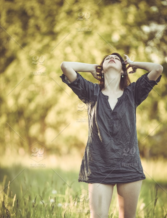 Young woman with long hair in a wet shirt posing in a