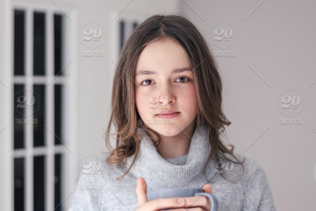 Nominated Close Up Portrait Of Beautiful Tween Girl In Warm Grey Pullover Holding Mug With Tea Looking At Camera Gray Background Natural Beauty No Makeup Stock Photo 9c860aa0 Bd17 415f 8fe0 8cf97f386d06