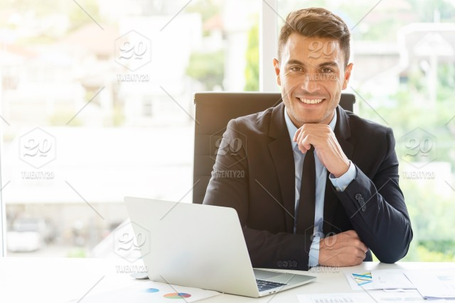 Portrait of handsome businessman sitting with smile in office.  Administrator, executive manager or boss concept.  20s,adult,background,business,businessman,casual,caucasian,cheerful,computer,confident,contemporary,cool,corporate,creative,design,desk  ...