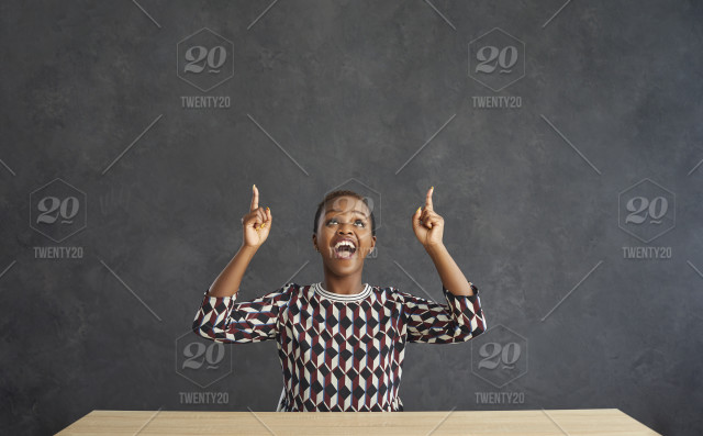 Overjoyed young African American woman sit at desk on