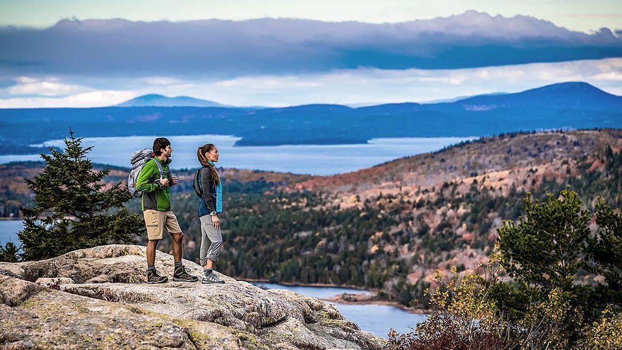 Mann und Frau mit Garmin Armbanduhren blicken von einem Gipfel aus in die Ferne