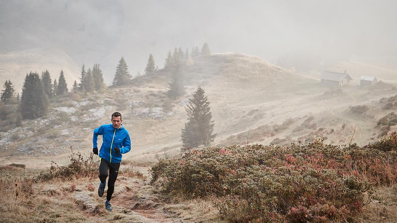 Trailrunner in Mizuno Laufschuhen beim Berglauf im Morgennebel