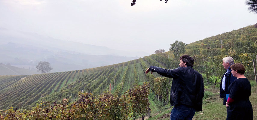 Emma Briffett of our tasting team and Sebastian Payne MW looking out over the at the vineyards at Coterno, Barolo