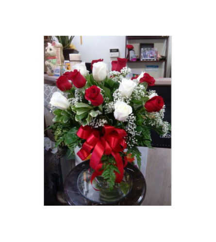 Red and white rose in clear vase by Vivian