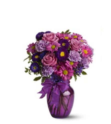 ASSORTED PURPLE FLOWERS ARRANGED LOOSE & AIRY IN A VASE