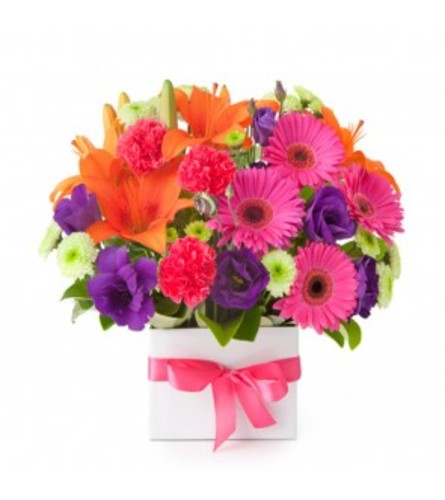 BRIGHT ASSORTED SUMMER FLOWERS ARRANGED IN A WHITE SQUARE VASE