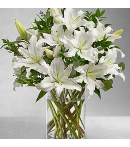 All white lilies and greens arranged in a glass vase