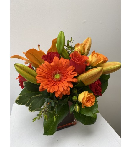 Summer Garden cube. A glass cube of mixed orange colored flowers