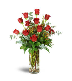 12 RED ROSES ARRANGED WITH ASSORTED FOLIAGE, IN A CLEAR OR RED VA