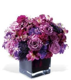 DENSE MIX OF PURPLE ROSES AND OTHER FLOWERS IN A LOW VASE