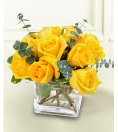 DOZEN YELLOW ROSES DENSELY ARRANGED IN LOW VASE
