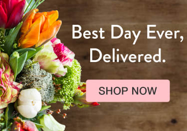 Colorful orange, pink, and green flower bouquet on a dark wood background - flower delivery in Henderson