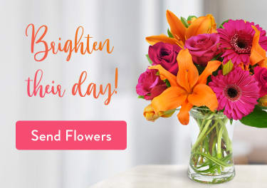 Flower arrangement of orange lilies and pink Gerbera daisies on a table - flower delivery in Vermilion