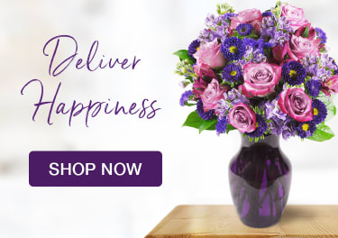 Arrangement of purple flowers and roses on a table - flower delivery in Garfield