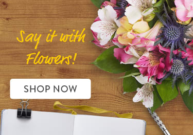 Multicolor flower bouquet on a desk with laptop and notebook - flower delivery in Ramsey