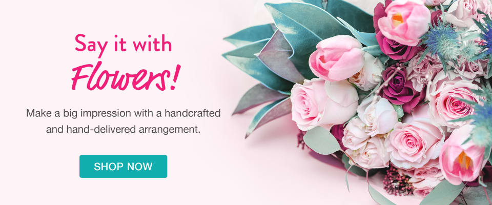 Light pink flowers with bright teal accents wrapped in a bouquet - flower delivery in Paramus