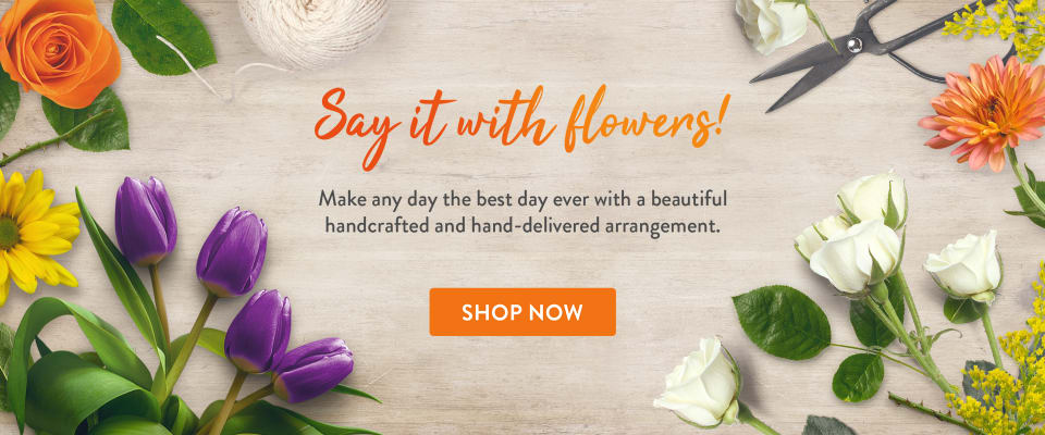 Purple tulips, orange roses, and colorful flowers on a table - flower delivery in Brimfield
