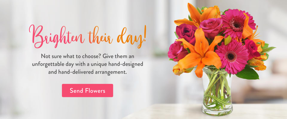 Flower arrangement of orange lilies and pink Gerbera daisies on a table - flower delivery in Oswego