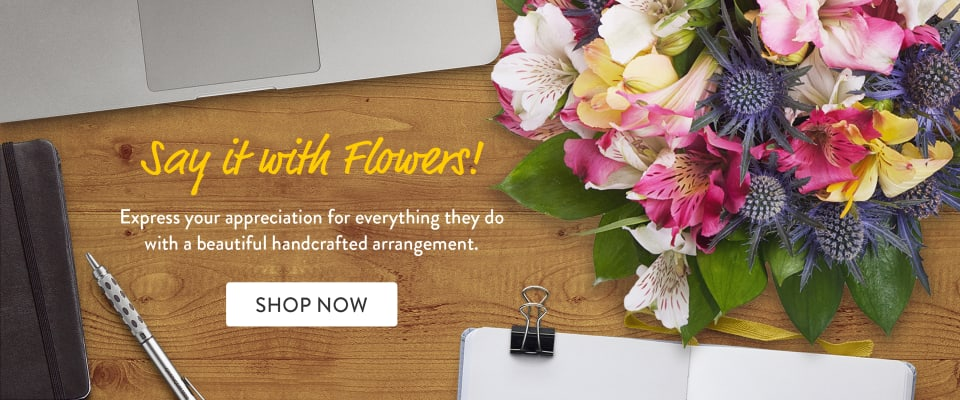 Multicolor flower bouquet on a desk with laptop and notebook - flower delivery in Hicksville
