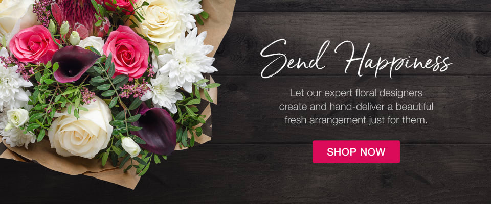 Vibrant pink roses, calla lilies, and white flowers in a wrapped bouquet on a dark wood surface - flower delivery in Yarmouth