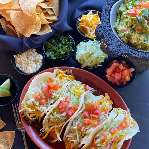 table of chips, guacamole and four prepared tacos with tomatoes lettuce and cheese