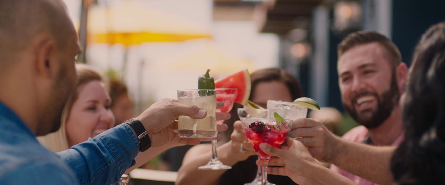 People's hands holding up beverages while dining together on the Uncle Julio's patio