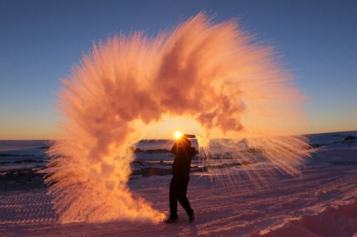 Photographer Michael Davies throws hot tea into the Artic air