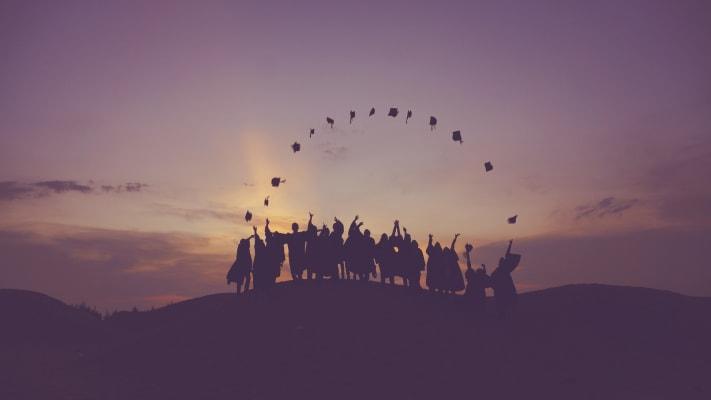 gruppo di studenti lancia il tocco al tramonto