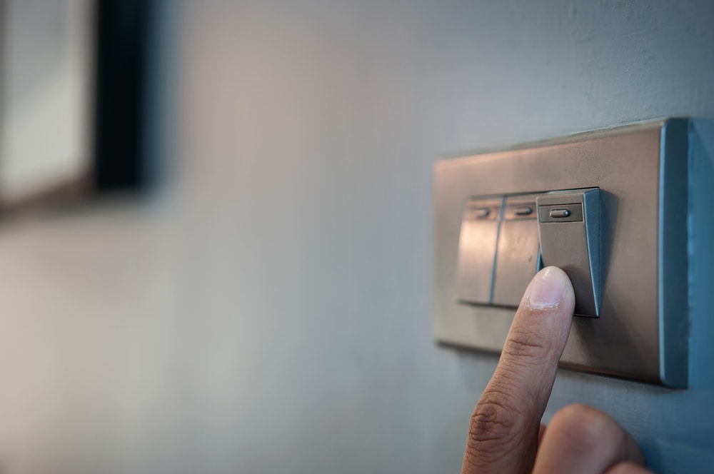 Tenant flipping a light switch in their new apartment