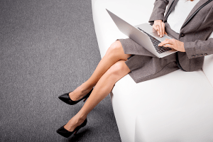 Woman working on laptop with her legs crossed