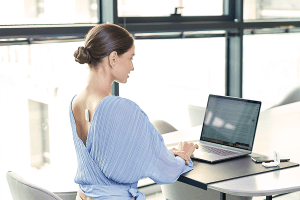 Woman wearing UPRIGHT GO 2 while working on laptop, demonstrating good posture in the office