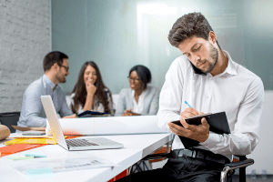Man holding phone between neck and shoulder; an example of bad posture in the office