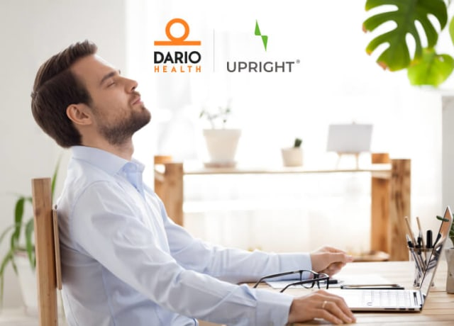 Man sitting back at desk looking relieved as he works